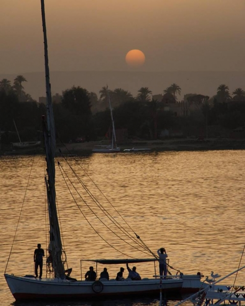 tourists watching sunset over Luxor city