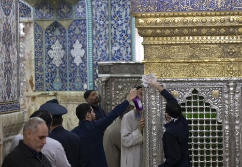 Staff members sanitizing the tomb of Hazrat Masoumeh as a Muslim (C) kisses the tomb, in the holy city of Qom 145Km (90 miles) south of Tehran following a Covid-19 outbreak in Iran, March 16, 2020.