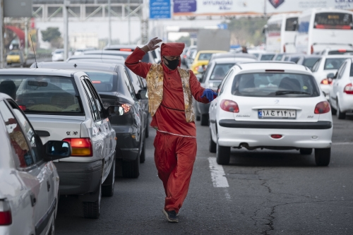 A man in red dresses wearing protective gloves and a face mask, dances as vehicles have stopped on the Tehran and Alborz provinces connecting road before a checkpoint for screening travelers who may be infected by the new coronavirus disease (Covid-19), in the west of Tehran, March 25, 2020.